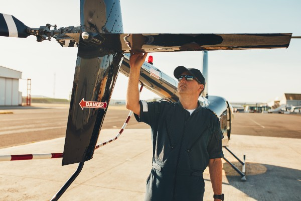 male-pilot-examining-helicopter-tail-wing-PFWYVWQ (1)